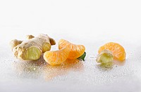 Ginger, Zingiber officinale root with Mandarin, Citrus reticulata, pieces arranged on silver background, and spritzed with water. Selective focus.
