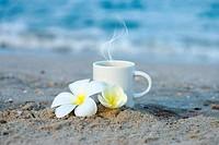 Coffee on the beach and frangipani flower.