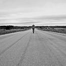 Caucasian girl standing on empty rural road