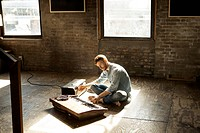 Young man playing synthesizer on floor
