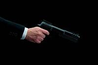 a man in a business suit firing a gun on black