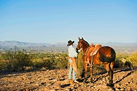 Caucasian rancher standing with horse on dirt field