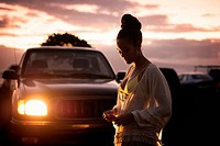 Teenage girl (16-17) standing in parking lot at dusk