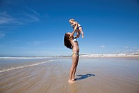 one year baby swimsuit fly in bikini woman mother arms at beach next to Conil Cadiz Spain.
