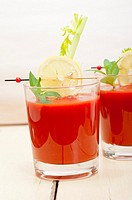 fresh tomato juice gazpacho soup on a glass over white wood table.