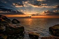 Beautiful ocean sunrise - calm sea and boulders with sky sun ra