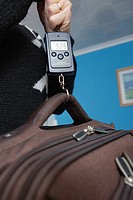 Weighing suitcase with digital scale for hand luggage on a flight.