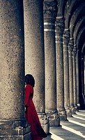 Mysterious woman in red dress behind column.