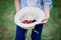 Still life, girl taking a straw hat with berries inside.
