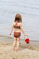 A four-year-old girl plays on the beach at Liberty Lake, Washington, USA.