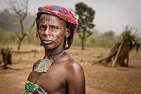 Portrait of a Mbororo woman with scars on her face and decorative necklace outside her hut.