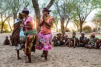 Group of women from the San tribe playing a game in which they dance in circles with their legs banded together in a remote village from the Kalahari ...