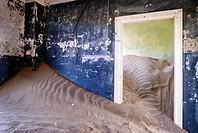 Room of an abandoned house full of sand from the desert.