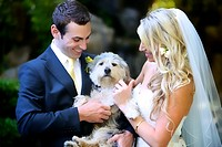 happy bride & groom petting dog on wedding day