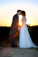 bride & groom kissing at sunset