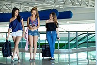 Group of 3 female teenagers with luggage at airport terminal.