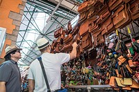 Two men shopping for leather bags at a stall in the Benito Juarez Market in Oaxaca Mexico.