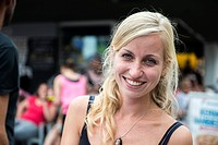 Tilburg, Netherlands. Young blonde and smiling woman visiting the annual fair´s LGBT / LGBTQ Pink Monday.