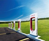 Tesla Supercharger new charging station with green nature scenery and blue sky in the background. Muskoka, Ontario, Canada.