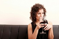 Portrait of a beautiful, latin Woman drinking red wine.