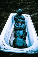 Chilling nightmare scene of a dumped bodybag laying in a countryside bathtub. Wake of a killers trail.