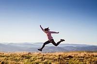 Happy girl jumping on the top of Goñiburu mountain.