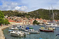 Boats in the harbour waterfront below the Spanish Fortress, Hvar Town, Croatia, Dalmatia, Dalmatian Coast, Europe.