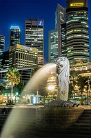 Night image of the brightly lit Merlion next to the Fullerton Hotel in the inner city of Singapore.