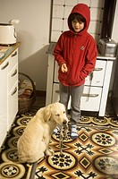 7 year old boy with his puppy dog beside heater in the kitchen