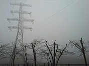 electrical pylon in field on a foggy day. Shot taken in Limburg province of the Netherlands.