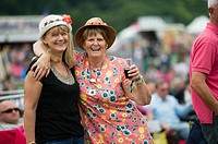 Two happy smiling laughing adult women enjoying the The Big Tribute Music festival, Aberystwyth, August Bank Holiday weekend, Summer 2015.