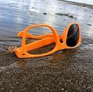 Dumped broken sunglasses near the sea on the beach.