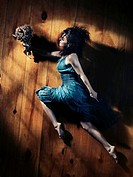 Young woman in a blue dress with a bouquet of wild flowers in a dynamic leap on wooden floor background, abstract artistic portrait in dramatic dim li...