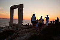 Tourists at the famous Portara, unfinished door of Apollon Temple, in town center at sunset, Naxos, Cyclades Islands, Greek Islands, Greece , Europe