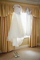 Brides wedding dress hanging up on the morning of the big day.
