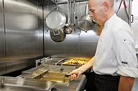 Chef deep frying food in a commercial kitchen in the UK.