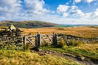 A gate in a stone wall on Wansfell on a sunny autumn day near Ambleside in the Lake District National Park, Cumbria, England.