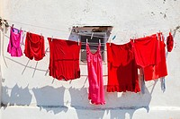 Italy, Procida - Red clothes on line drying in the sun.