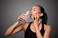 Beautiful healthy black asian woman enjoying drinking glass of water.