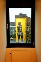 Woman taking self portrait of her reflection in a window.