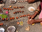 women hands lit small oil lamps near temple in thiuvannamalai, india