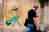Young man wearing tattoos walking down a street passing next to street art on a stone wall, Bordeaux, France.