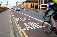 cyclist in empty bus lane in early morning traffic Belfast city centre Northern Ireland.