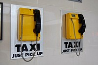 yellow dedicated taxi phone pickup lines in transport hub Belfast Northern Ireland.