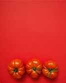 Red tomatoes on red background.