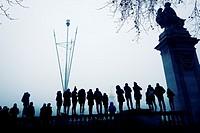 Silueta de gente de pie sobre una barandilla mirando, al fondo Victoria Memorial. Buckingham palace, Westminster, London, UK, Europa.