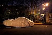 Coche aparcado en la calle protegido con un toldo de noche con farolas y luces encendidas en las ventanas de las viviendas. Princes Gardens, Knightsbr...