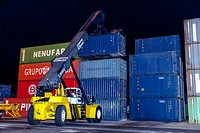 reach stacker lifting containers in a dock at night