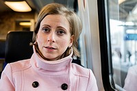 Tilburg, Netherlands. Young adult caucasian female commuting by intercity train to her assignmenet as a musical teacher.