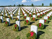 Rows of grave stones with wreaths & red bows in Sarasota National Cemetery in Sarasota Florida.
